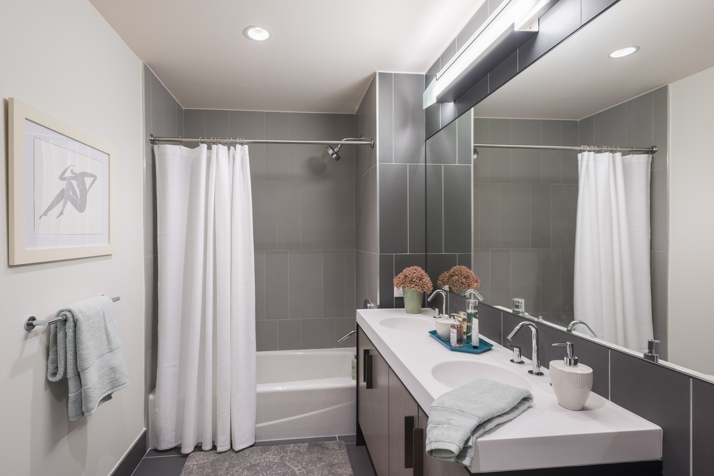 The Ashland: PH2B a shower that has a sink and a mirror