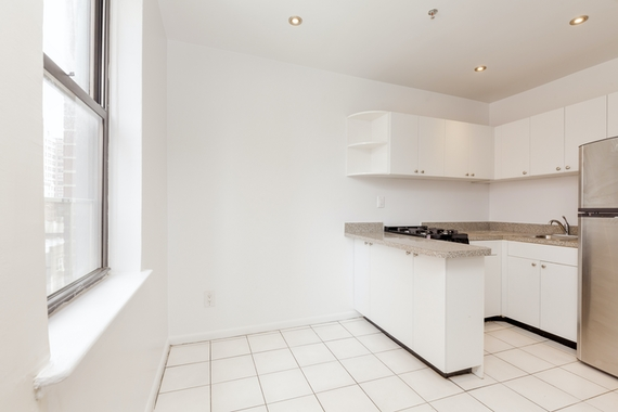 a kitchen with white cabinets and a window