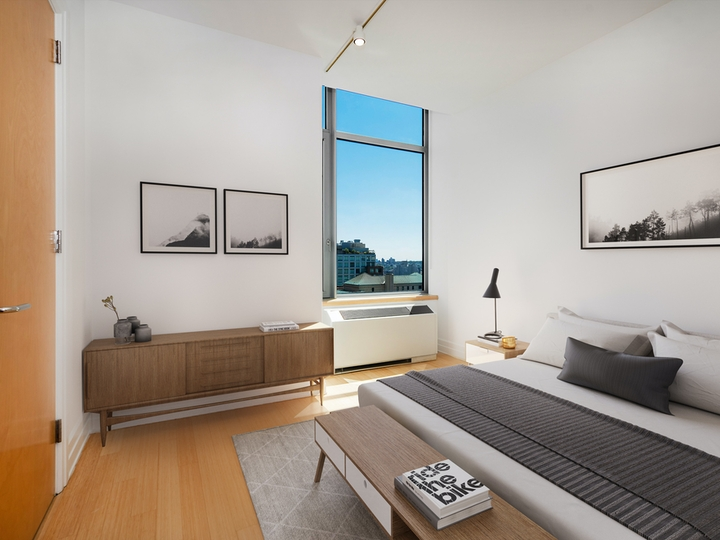 a bedroom with a bed and a mirror in a room