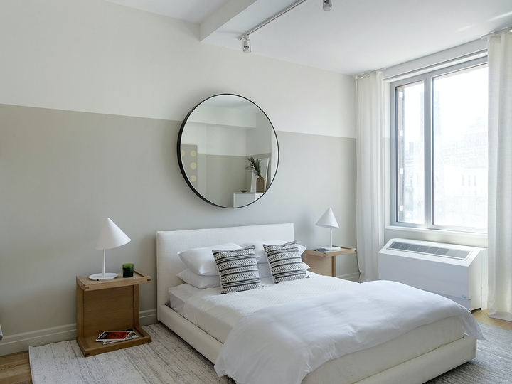 a bedroom with a bed and a mirror