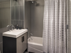 Thumbnail of The Ashland: 28B a white tub sitting next to a shower curtain
