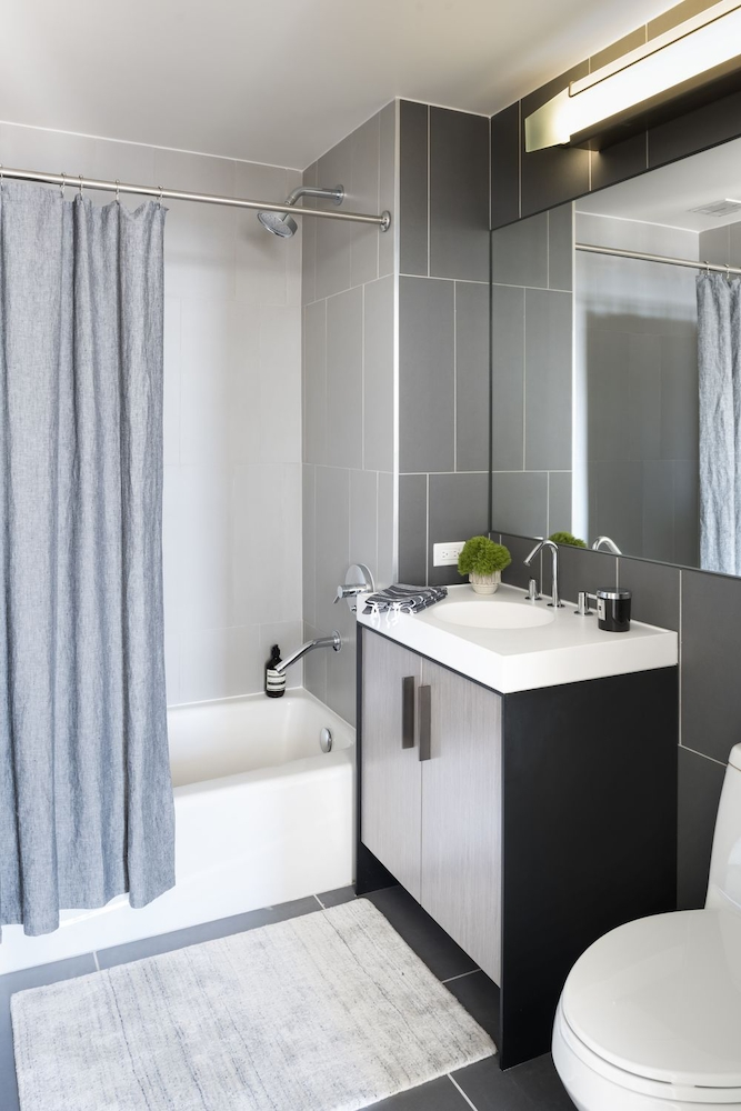 The Ashland: 28D a white tub sitting next to a shower