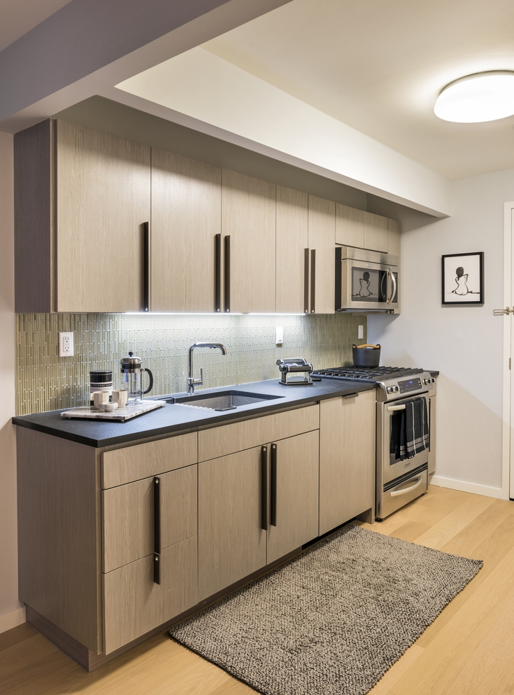 The Ashland: 24B a modern kitchen with stainless steel appliances and wooden cabinets