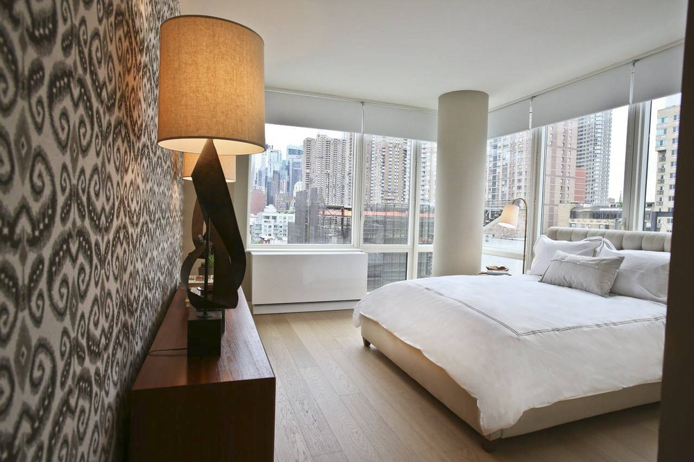 Gotham West: 3008 a large white bed sitting next to a window