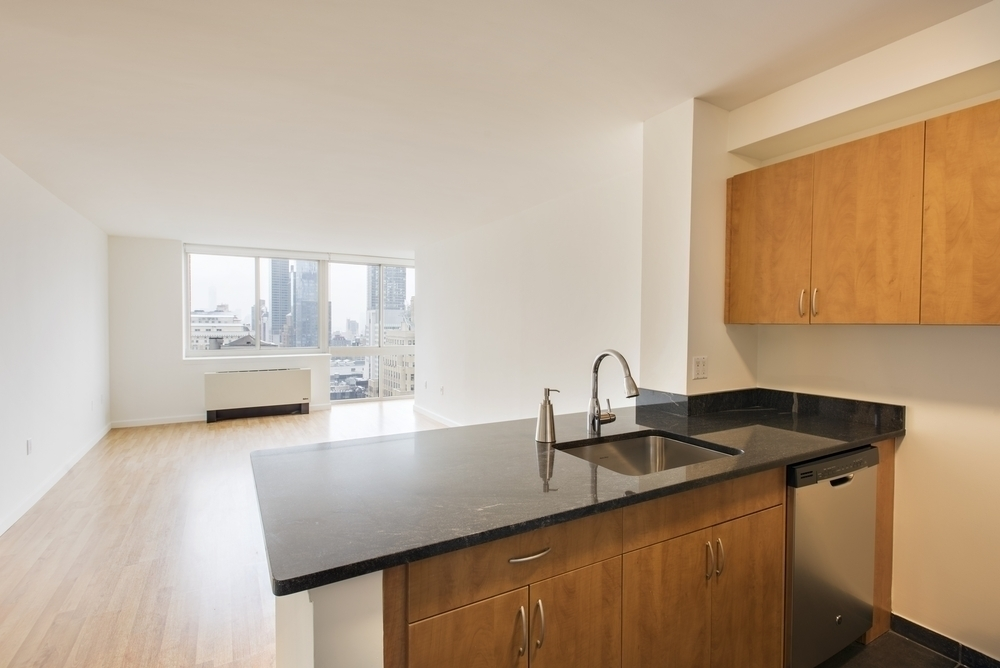 Atlas New York: 16D a kitchen with stainless steel appliances and wooden cabinets