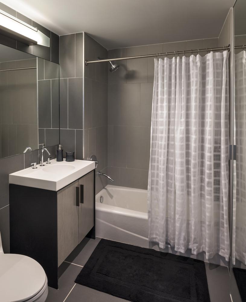 The Ashland: 37B a white tub sitting next to a shower curtain