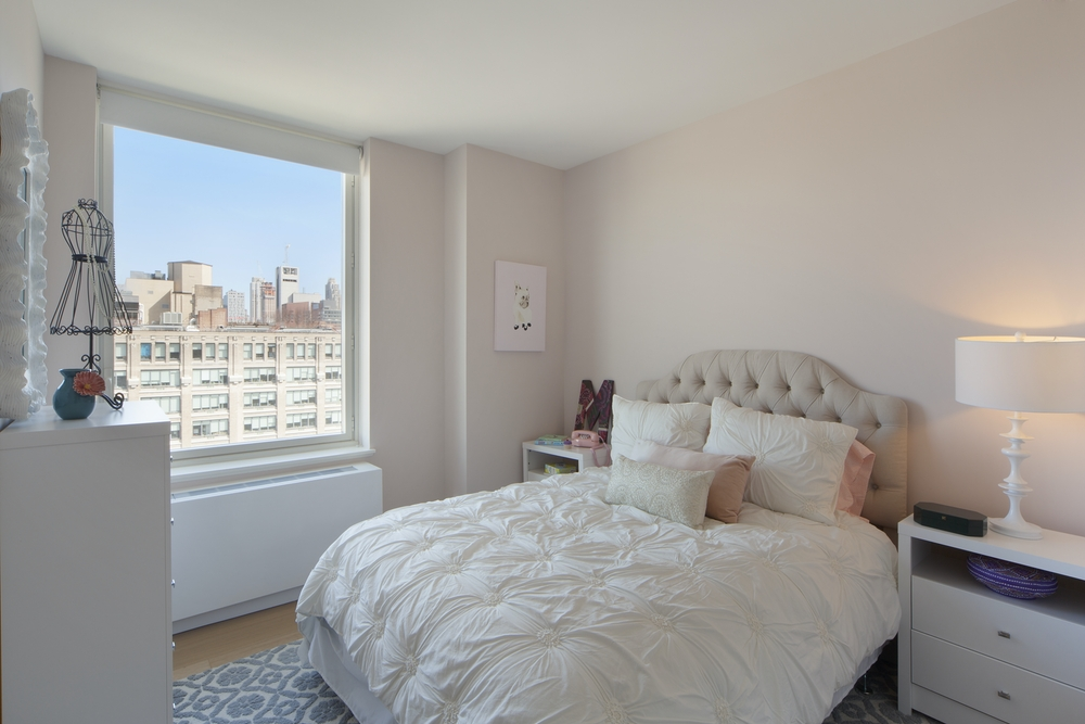 Gotham West: 422 a bedroom with a bed and desk in a room