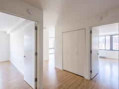 Thumbnail of The Nicole: 7E a large empty room with a wood floor