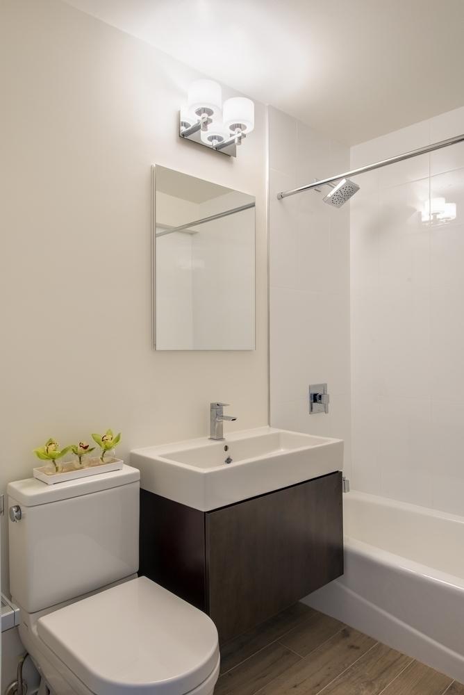 Atlas New York: 9J a white sink sitting under a mirror