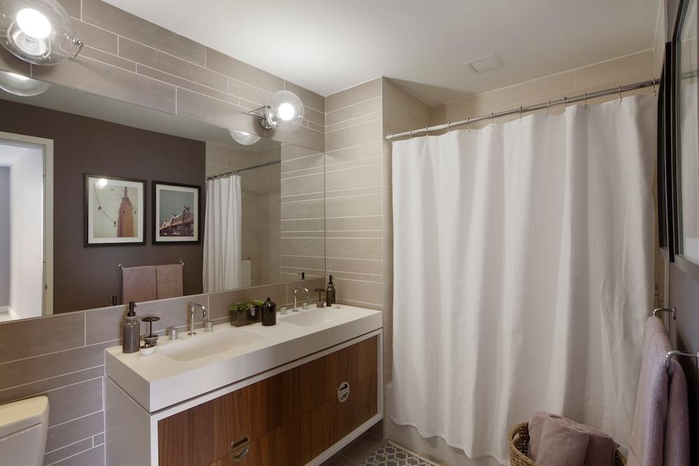 Gotham West: 1502 a white sink sitting under a mirror next to a shower