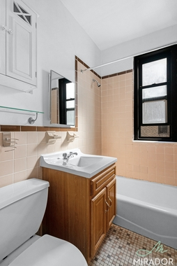 a bedroom area with a sink and a window