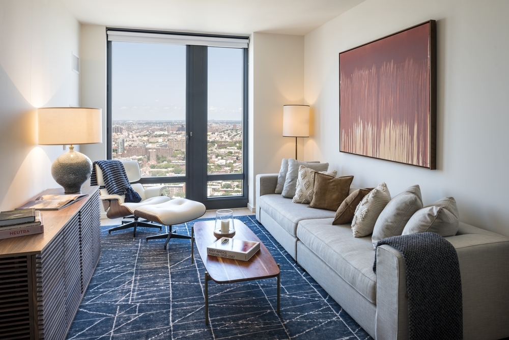 The Ashland: 27N a living room filled with furniture and a large window