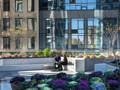 Thumbnail of The Ashland: 37G a vase of flowers sitting on a bench in front of a building