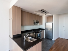 a modern kitchen with stainless steel appliances and wooden cabinets