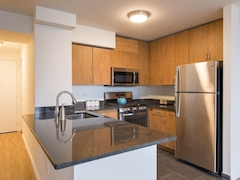 Thumbnail of Atlas New York: 14H a modern kitchen with stainless steel appliances and wooden cabinets