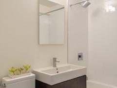 Thumbnail of Atlas New York: 26E a white sink sitting under a mirror