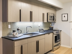 Thumbnail of The Ashland: 35B a modern kitchen with stainless steel appliances and wooden cabinets