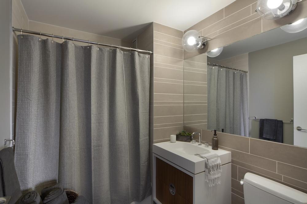 Gotham West: 2107 a white sink sitting next to a shower curtain