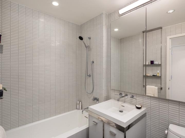 a white sink sitting under a window next to a shower