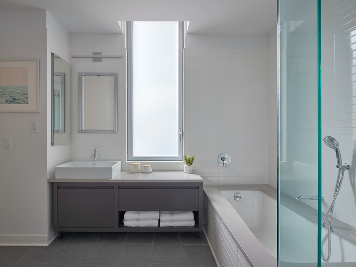 a large white tub next to a window