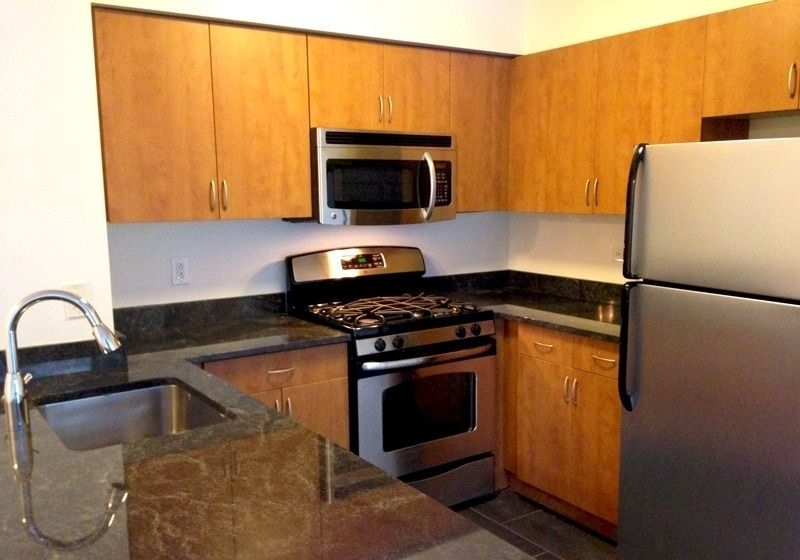 Atlas New York: 15F a kitchen with a stove top oven sitting inside of a refrigerator
