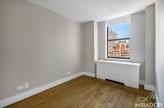 a room with white walls and a large window