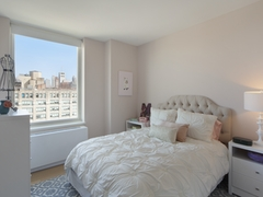 Thumbnail of Gotham West: 1208 a bedroom with a bed and desk in a room