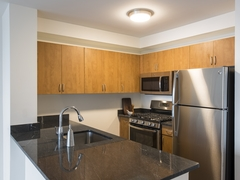Thumbnail of Atlas New York: 11B a modern kitchen with stainless steel appliances and wooden cabinets