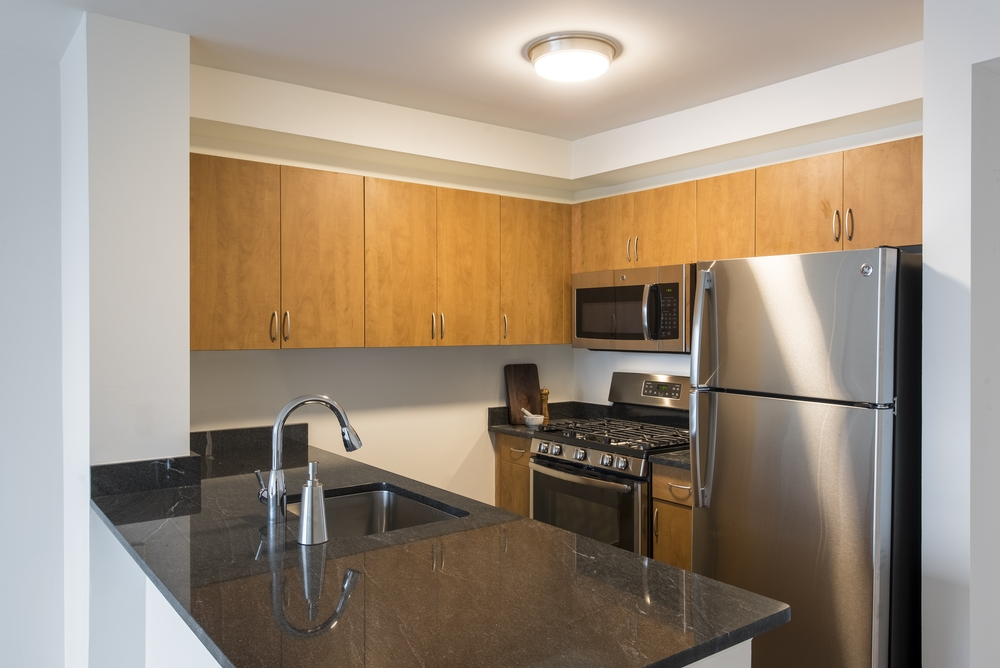Atlas New York: 11B a modern kitchen with stainless steel appliances and wooden cabinets
