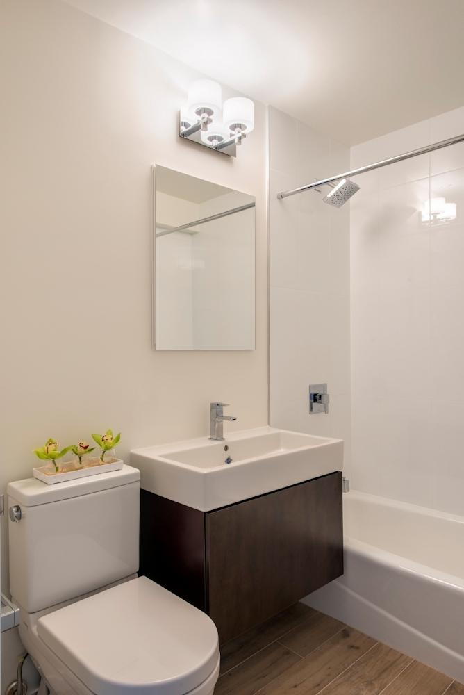 Atlas New York: 14H a white sink sitting under a mirror