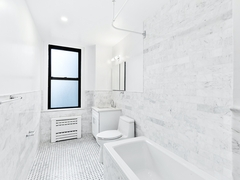 a white tub sitting next to a window