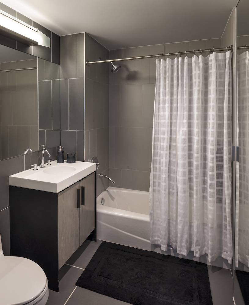 The Ashland: 33F a white tub sitting next to a shower curtain