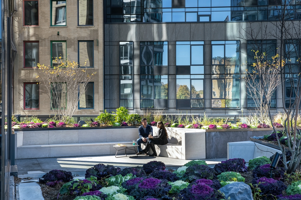 The Ashland: 46J a vase of flowers sitting on a bench in front of a building
