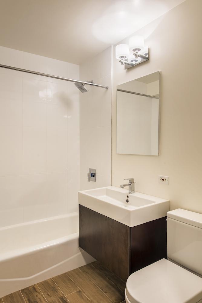Atlas New York: 15B a white sink sitting under a mirror