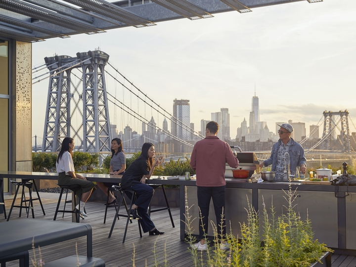 a group of people sitting at a table with a bridge in the background