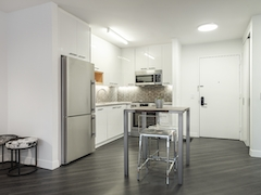 a room filled with furniture and a refrigerator in a kitchen