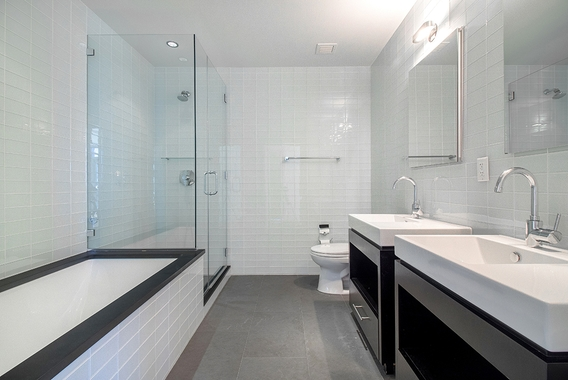 a large white tub sitting next to a glass shower door