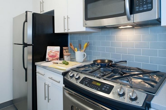 a stove top oven sitting inside of a kitchen with stainless steel appliances