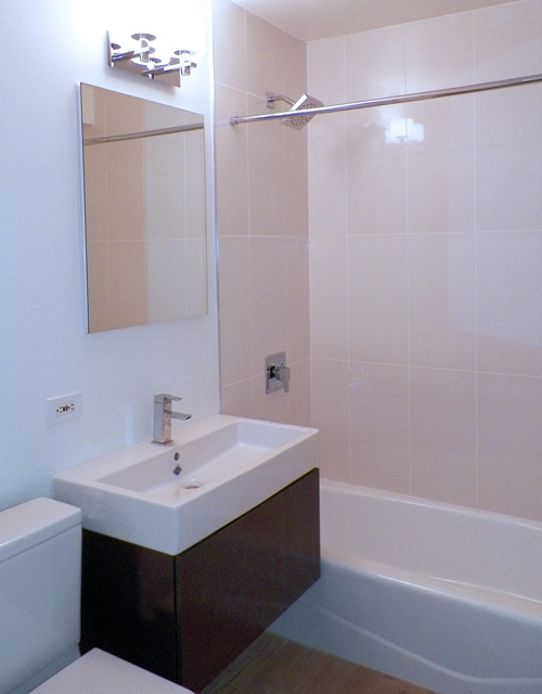 Atlas New York: 17A a white tub sitting next to a sink