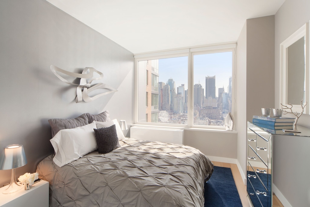 Gotham West: 918 a bedroom with a bed and desk in a room