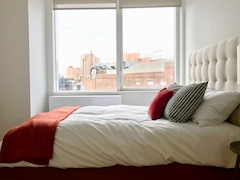 a large white bed sitting next to a window