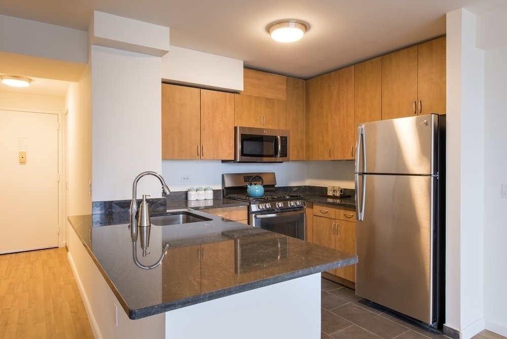Atlas New York: 05B a modern kitchen with stainless steel appliances and wooden cabinets