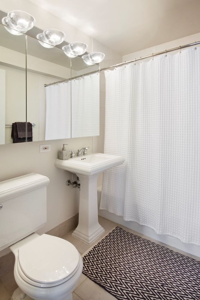 Atlas New York: 27B a white sink sitting next to a shower