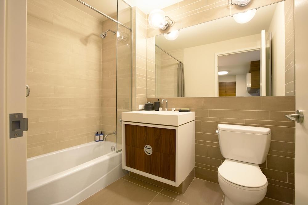 Gotham West: 1005 a white sink sitting under a mirror