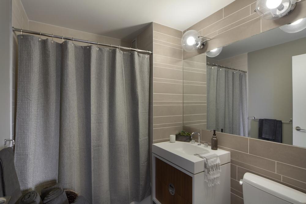 Gotham West: 2817 a white sink sitting next to a shower curtain