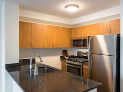 Thumbnail of Atlas New York: 17A a modern kitchen with stainless steel appliances and wooden cabinets
