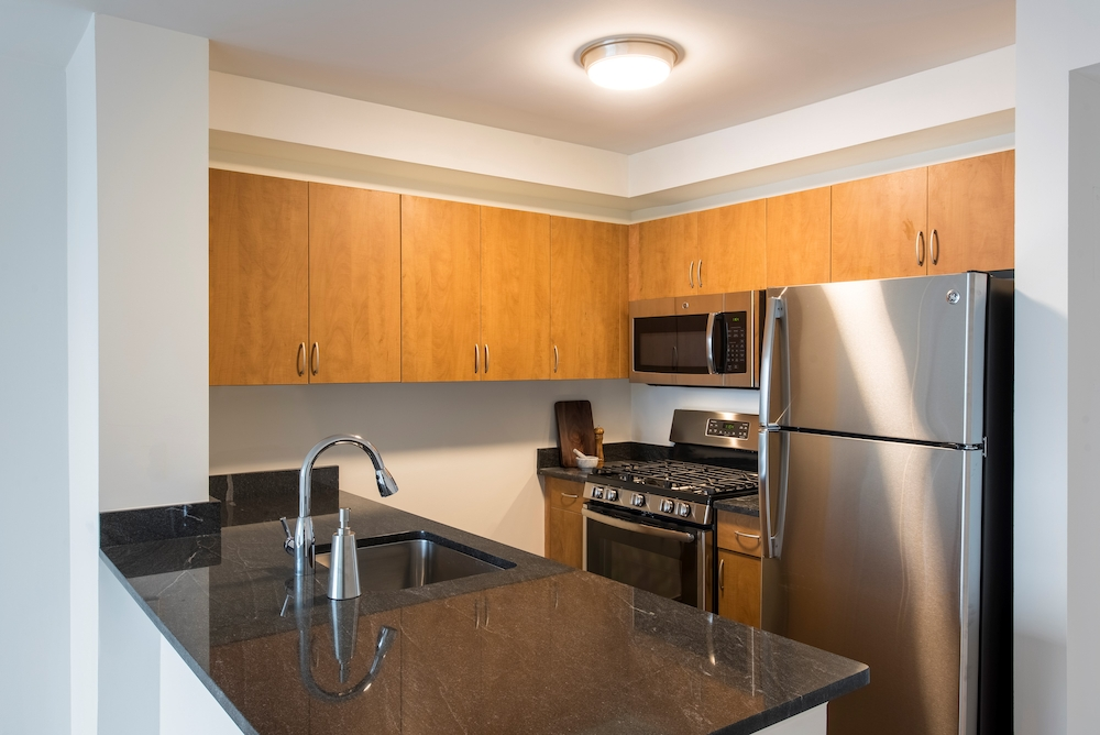 Atlas New York: 17A a modern kitchen with stainless steel appliances and wooden cabinets